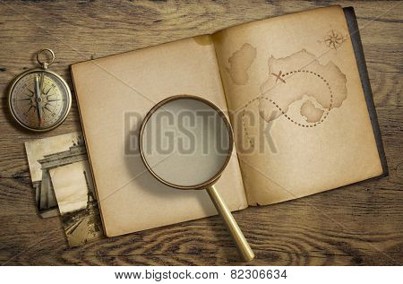 Adventure and travel nautical theme. Diary with map and magnifying glass on wooden table