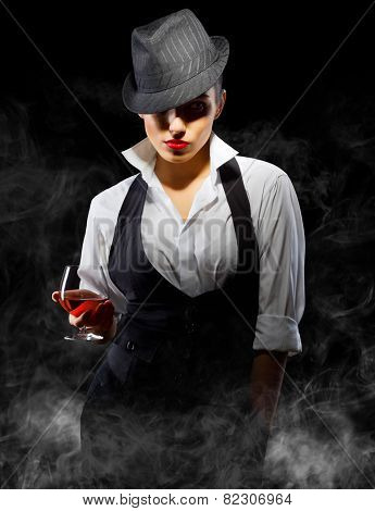 Young woman in manly style with brandy glass on smoke background