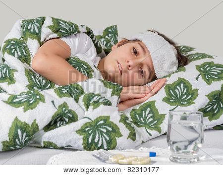 Sick boy lying in bed with high fever