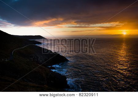 Sunrise near Langland Bay, on the Gower Peninsula, South Wales, with the Wales Coast path snaking across the cliffs.