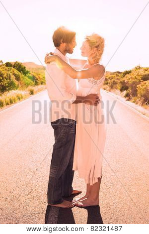 Attractive couple embracing barefoot on the road on a sunny day