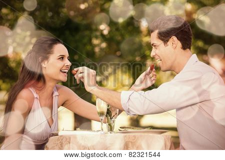 Smiling young couple with champagne flutes feeding strawberries to each other at an outdoor caf�?�©