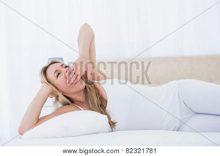 Blonde woman lying in bed yawning at home in the bedroom