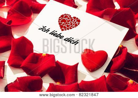 ich liebe dich against card with red rose petals