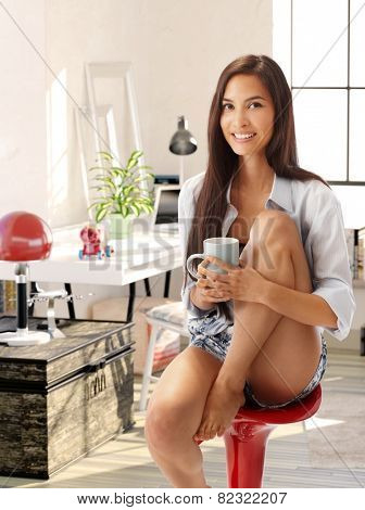 Attractive young casual woman sitting at home on chair hugging her pulled up leg, smiling, drinking tea.