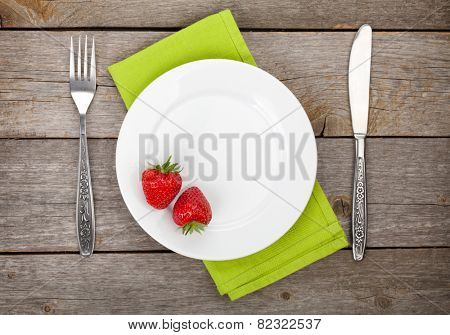 Plate with ripe strawberry and silverware over old wooden table