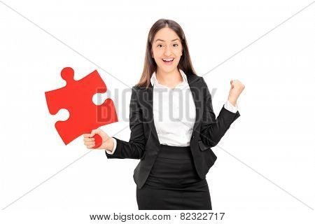 Delighted businesswoman holding a piece of puzzle isolated on white background
