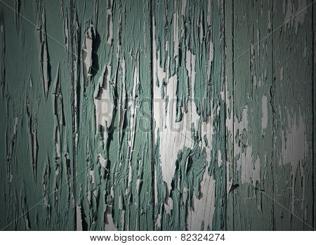 Closeup of green flaking paint on boards