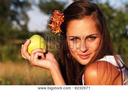 Mujer sosteniendo la manzana con flor en el pelo