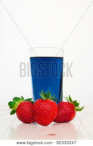 Glass with cold blue Thai tea and strawberries