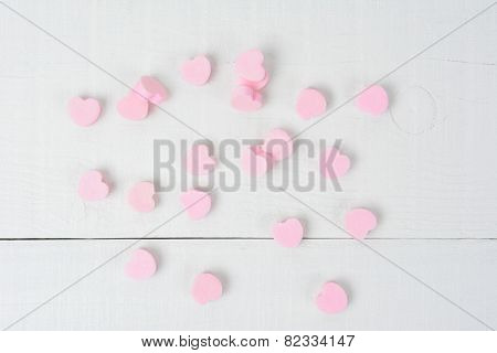 Overhead shot of a group of pink Valentine's Day candy hearts on a white wood table. The hearts are blank. Horizontal format.