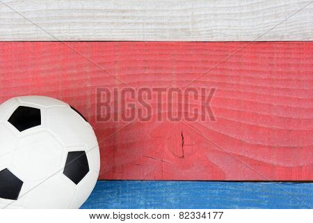 High angle shot of a soccer ball on a red, white and blue picnic table. Horizontal format with copy space. Suitable for American Holidays: 4th of July and Memorial Day,