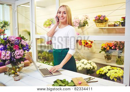 Friendly shop assistant speaking on the phone and using laptop in the shop