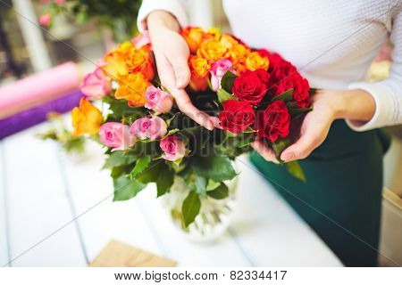 Female florist hands touching fresh rosebuds