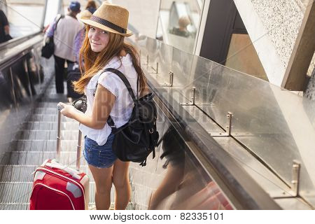 Young cute girl with the red suitcase standing on the escalator. Travel concept.
