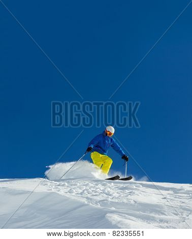 Male skier on downhill free-ride with sun and mountain view