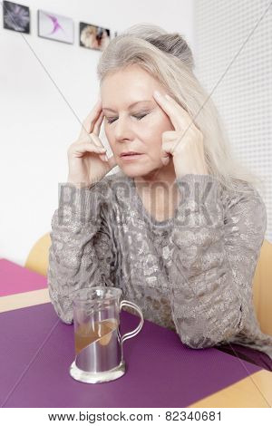 An image of a best age woman with headache and a cup of tea