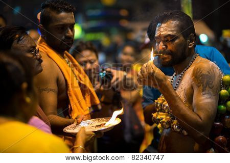 KUALA LUMPUR, MALAYSIA - FEBRUARY 3, 2015: A Hindu devotee lights up a cigar as part of the ritual for a ceremony at the Batu Caves temple on Thaipusam day, a day of thanksgiving and devotion.