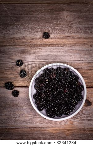 A white bowl filled with blackberries on an old wooden table. Overheard view. Retro style processing with vignette.