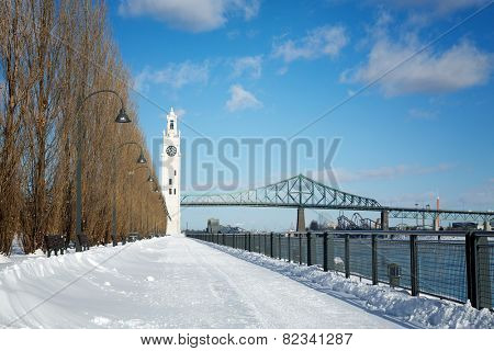 Snow drifts across the path to the Tour de l'Horloge, Montreal Clock Tower, with the Jaques Cartier Bridge in the background. In Old Port, Montreal Quebec, Canada