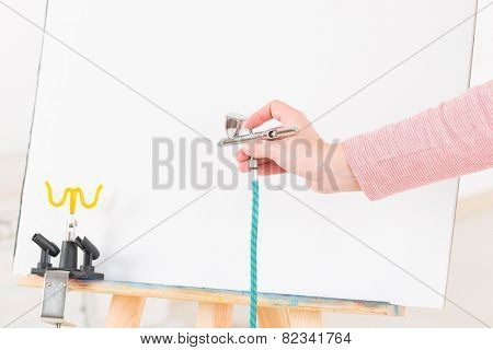 Hand holding a professional airbrush over white canvas or background