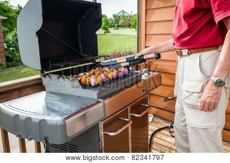 Man set shish kebob skewers on a grill
