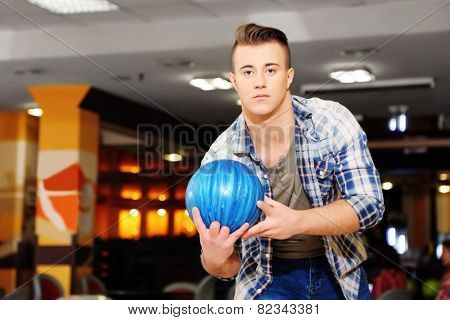 Young man playing bowling in club