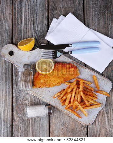 Breaded fried fish fillet and potatoes with sliced lemon and cutlery on cutting board and wooden planks background