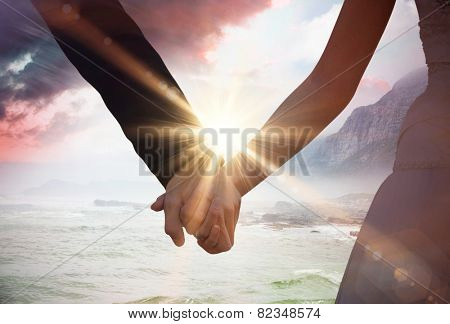 Mid section of newlywed couple holding hands in park against sunrise over magical sea