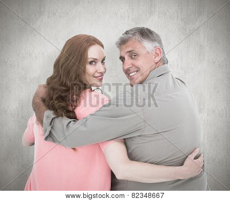 Casual couple standing arms around against white background