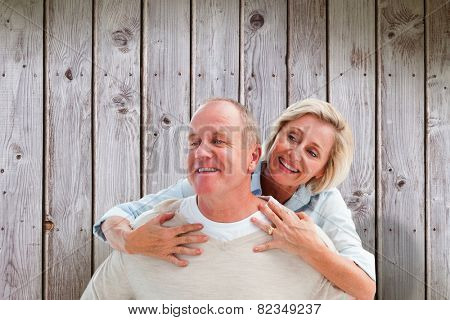Happy mature man giving piggy back to partner against wooden planks