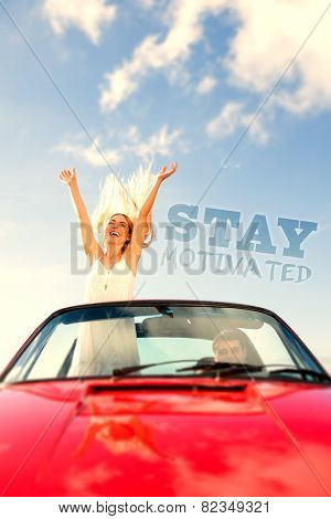 Happy woman standing in cabriolet while her boyfriend driving against stay motivated