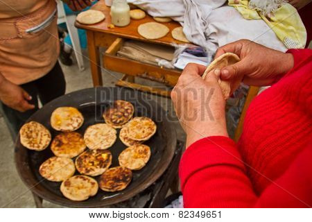 Indigenous woman making corn tortillas in a Cuenca local market