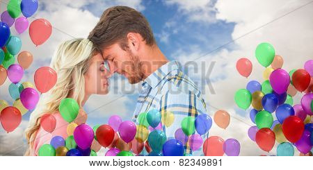 Attractive couple standing touching heads against blue sky with white clouds