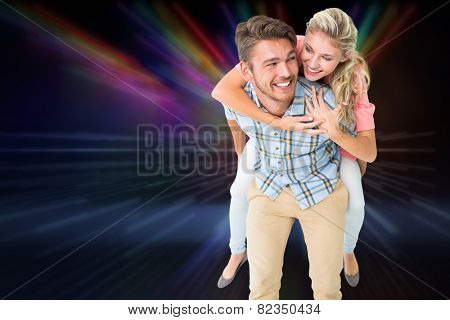 Handsome man giving piggy back to his girlfriend against cool nightlife lights