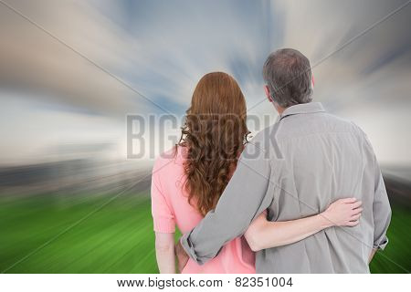 Casual couple standing arm around against cloudy sky over city