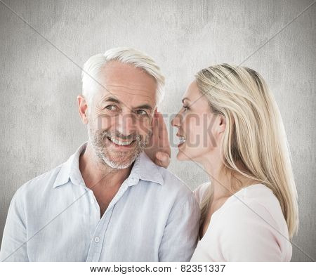 Woman whispering a secret to husband against weathered surface