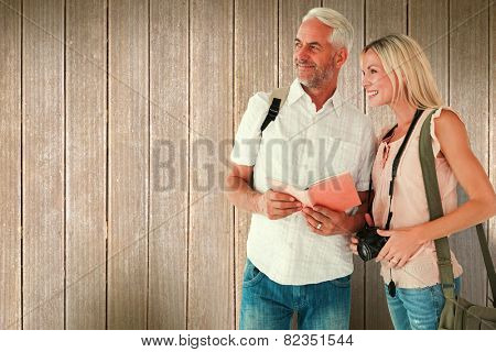 Happy tourist couple using the guidebook against wooden planks