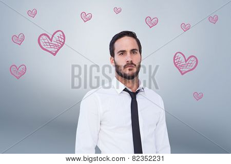 Unsmiling businessman standing with hands in pockets against grey vignette
