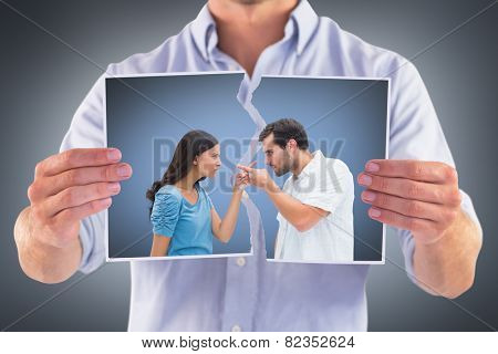 Angry couple pointing at each other against grey vignette