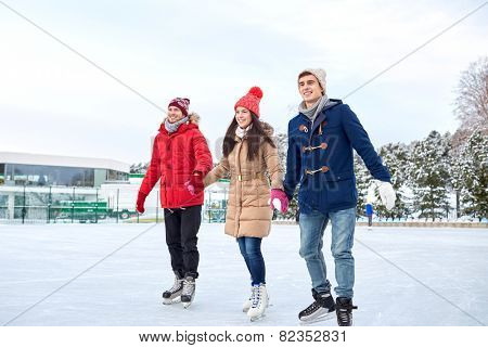 people, winter, friendship, sport and leisure concept - happy friends ice skating on rink outdoors