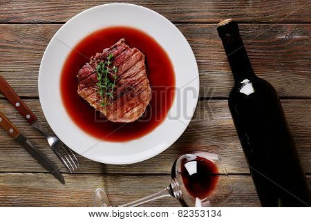 Grilled steak in wine sauce with bottle of wine on wooden background