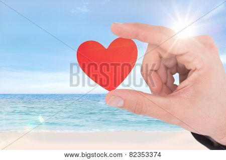 Businessman measuring something with his fingers against beach scene