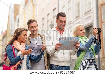 travel, vacation, technology and friendship concept - group of smiling friends with city guide, photocamera and map exploring city