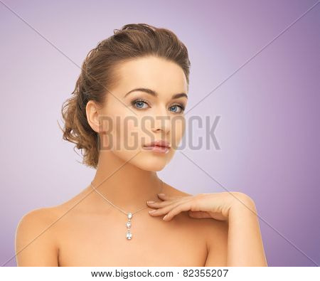 beauty, people and jewelry concept - beautiful young woman wearing shiny diamond pendant over violet background