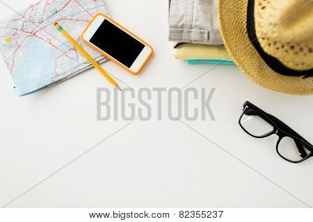 travel, summer vacation, tourism and objects concept - close up of folded clothes, smartphone and touristic map on table