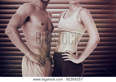 Mid section of a fit young couple against grey shutters