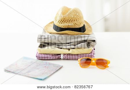 travel, summer vacation, tourism and objects concept - close up of folded clothes and touristic map on table at home