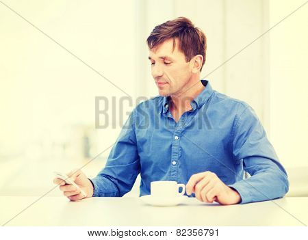 business, communication, modern technology concept - buisnessman with smartphone and cup of coffee