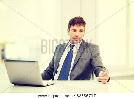 technology, business and office concept - puzzled businessman working with laptop computer and documents